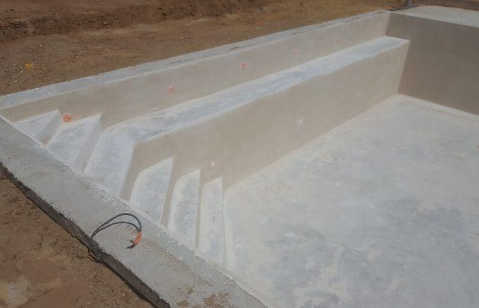piscine monobloc à débordement banquette escalier