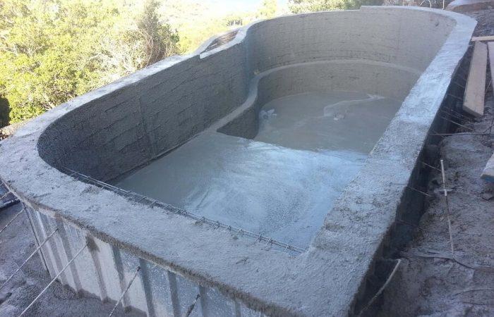 piscine monobloc en forme avec débordement coulage béton armé